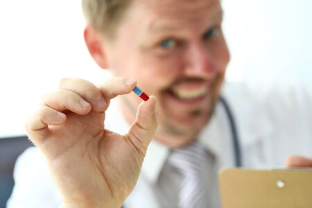 GP holding in arm little pill offering it to patient close-up. Illness prevention pharmacology and healthy life concept Stock Photo