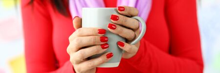 Letterbox view of female hands with red nails holding gray cup of coffee close-up