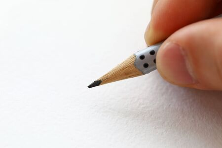 Male hand holding simple pencil ready to draw something on white paper macro 스톡 콘텐츠