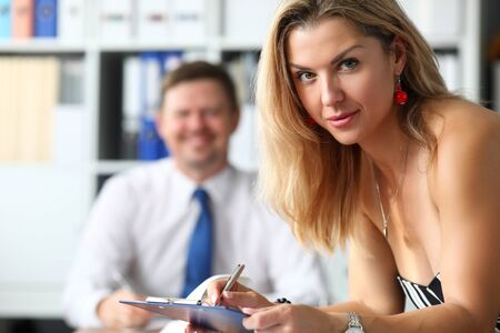 Blonde mature attractive woman standing at office workplace listening to opponent portrait