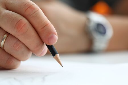 Male arm holding black simple pencil ready to draw something on white paper macro
