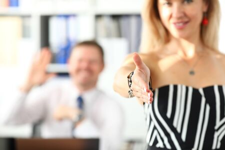 Smiling office clerk welcoming business partner by shaking hand as sign of future achievements and prospects closeup with colleague in background Фото со стока