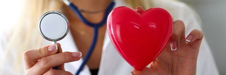 Female medicine doctor hold in hands red toy heart and stethoscope. Cardio therapeutist, student education, physician make cardiac physical, heart rate measure, arrhythmia concept Stock Photo
