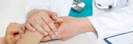 Beautiful female doctor holding patients hand for encouragement and empathy and touching her arm. Partnership, trust and medical ethics concept. Bad news lessening and support. Patient cheering Stock Photo