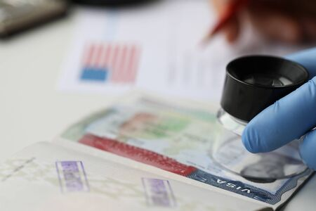 Specialist with loupe checking authenticity of american in passport close-up
