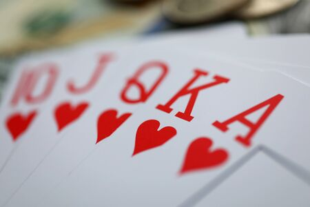 Playing cards lying at money stake with royal flush combination close-up
