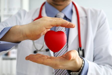 Male medicine doctor hands holding and covering red toy heart closeup. Cardio therapeutist student education physician make cardiac physical heart rate measure arrhythmia concept Stockfoto - 135492223
