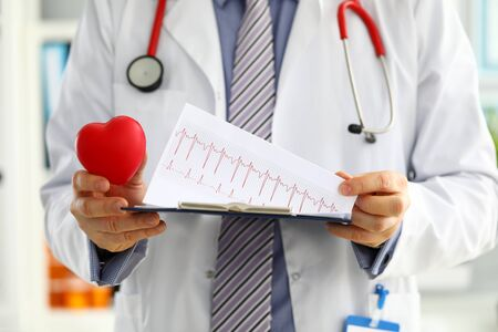 Male medicine doctor hands holding red toy heart and cardiogram chart on clipboard closeup. Cardio therapeutist physician make cardiac physical heart rate measure arrhythmia concept