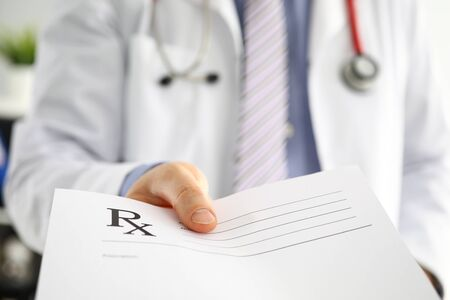 Male medicine doctor hand hold and give prescription form to patient closeup. Panacea life save prescribe treatment legal drug store contraception concept. Empty form ready to be used 写真素材