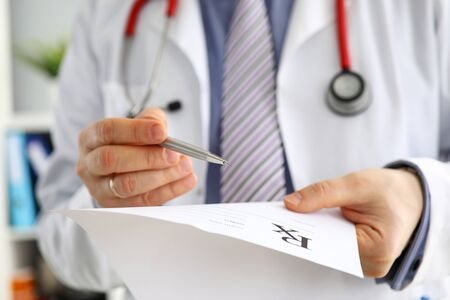 Male medicine doctor hand hold clipboard pad and give prescription to patient closeup. Panacea, life save prescribe treatment legal drug store contraception concept. Empty form ready to be used 写真素材
