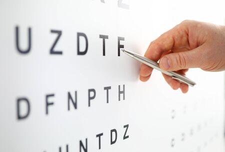Silberner Kugelschreiber, der auf den Buchstaben in der Sehprüftabelle zeigt. Sehtest und Korrektur ausgezeichnetes Sehvermögen oder Optikergeschäft Laserchirurgie alternatives Konzept für die Gesundheitsbescheinigung des Fahrers Standard-Bild