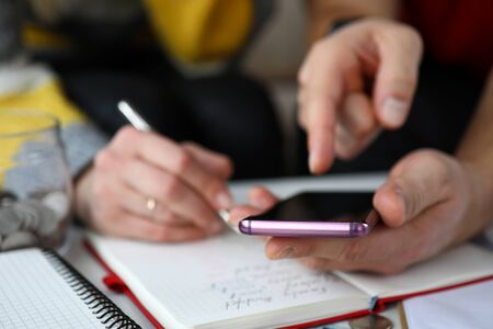 Close-up of mans hands holding mobile phone and calculating on telephone. Woman writing down in notebook. Months expenses. Family budget and finance concept Standard-Bild