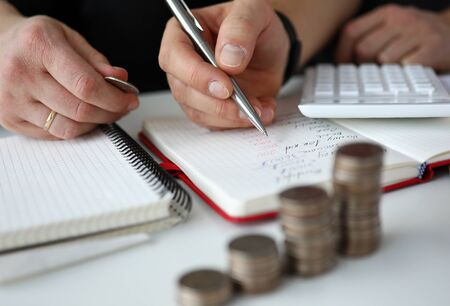 Close-up of man calculating total amount of expenses in month. Notebook with remarks. Coins and calculator on table. Family budget finance and economy concept Reklamní fotografie