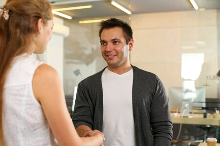 Portrait of business partners handshaking after having deal at office. Happy smiling man looking at woman with gladness.Teamwork and signing profitable bargain concept