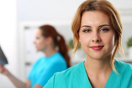 Primo piano di bello lavoratore medico sicuro in uniforme speciale. Medicina moderna e innovazione. Concetto di assistenza sanitaria e check-up. Infermiera sullo sfondo Archivio Fotografico