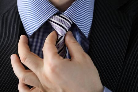 Close-up view of man straightens striped tie. Macro shot of corporate male in stylish suit adjusting necktie. Getting ready for business meeting concept Archivio Fotografico