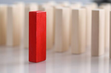 Close-up view of one red wooden block with many unpainted bricks on background. Symbol for individuality and uniqueness. Stand out from the crowd and different thinking concept