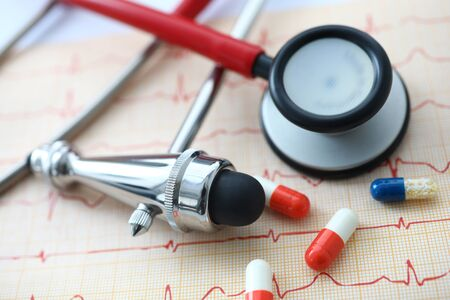 Medical instruments and pills lying at electrocardiogram paper close-up Stock Photo