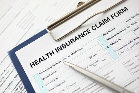 Zilveren pen liggend op aanvraagformulier bij verzekeringsagent werktafel in bedrijfskantoor close-up