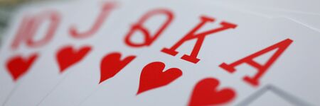 Letterbox view of playing cards lying at money stake with royal flush combination close-up