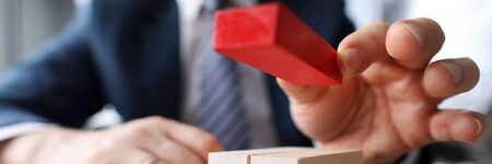 Close-up view of businessmans hand putting red block on small bunch of other bricks. Office worker in suit. Metaphor to management and business organization concept