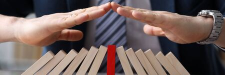 Close-up view of businessmans hands protecting line of wooden blocks. Colourless bricks with one red cube in the middle. Business defending and planning concept