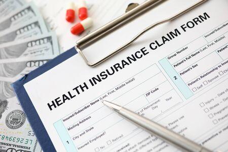 Pluma de plata en formulario de solicitud en la mesa de trabajo del agente de seguros en la oficina de la empresa closeup