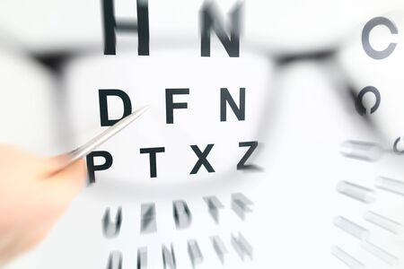 Silver pen pointing to letter in check table through eyeglasses. Sight test and correction excellent vision or optician shop laser surgery alternative health certificate examination concept