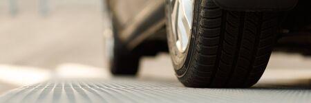 Automobile scura che sta sulla vista del pavimento d'acciaio da sotto. Problemi di parcheggio, salone dell'automobile o esposizione, pneumatici per la stagione invernale, prestito finalizzato al cliente, controllo ufficiale dei veicoli o concetto di esame