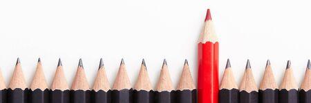 Rood potlood dat zich onderscheidt van de menigte van identieke zwarte kerels op witte tafel. Leiderschap, uniciteit, onafhankelijkheid, initiatief, strategie, afwijkende mening, anders denken, zakelijk succesconcept