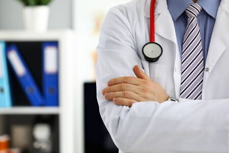 Male medicine doctor hands crossed on his chest in office. Medic store physical and patient disease prevention er consultant body 911 profession pulse measure healthy lifestyle concept Stockfoto