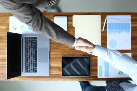 Two business person striking hands on bargain over worktable full of financial statistics close-up