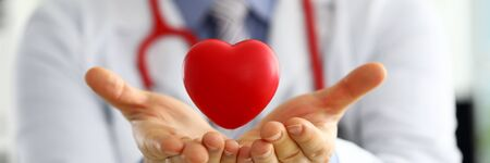 Male medicine doctor hands holding and covering red toy heart closeup. Cardio therapeutist student education physician make cardiac physical heart rate measure arrhythmia concept Stock Photo