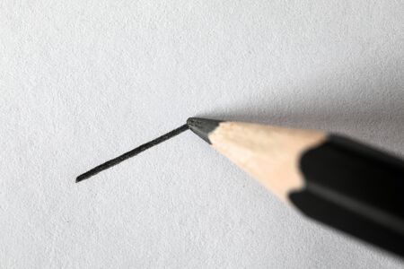 Close-up of black graphite pencil drawing perfectly straight line on textured white sheet. Short direct distance on piece of paper. Art and painting concept
