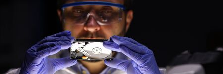 Portrait of specialist in eyewear looking at rigid disc. Man examining pc detail. Worker checking detail condition. Small hard disk for computer. Electronics and technique concept