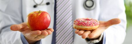 Doctor in office holding in hand pink doughnut vs red apple close-up. Products that can not be consumed in certain diseases concept