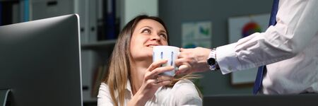 Man brought woman cup tea workplace coffee break. Increase employee productivity. Emotional exhaustion and decline, lack of energy. Positive emotions from attention employees at work Zdjęcie Seryjne