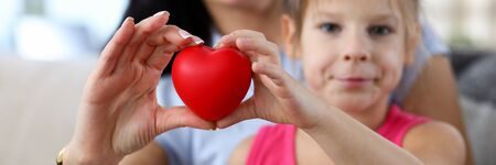 Focus on hands of happy mother and little daughter hands holding toy red heart. Love relationship between mum and child. Friendly family and motherhood concept