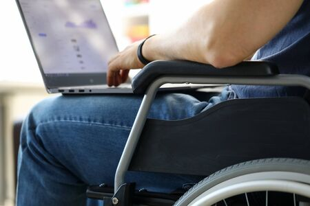 Man sitting in wheelchair working with laptop computer concept