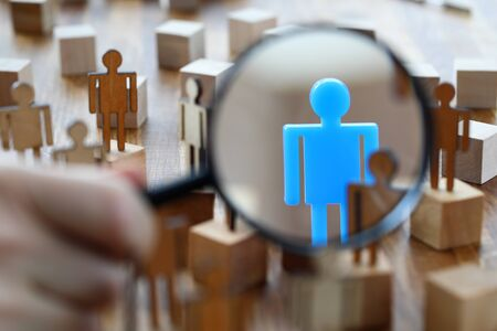 Searching for missing person in crowd of toy human figures with magnifying glass closeup