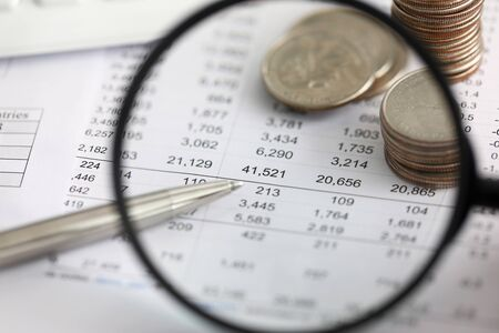 View at financial details in table thru magnifying glass close-up