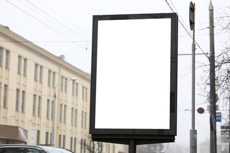 Close-up of billboard with empty copy space on screen. Blank poster with place for text ready for new advertisement. Ad concept. Cityscape on background