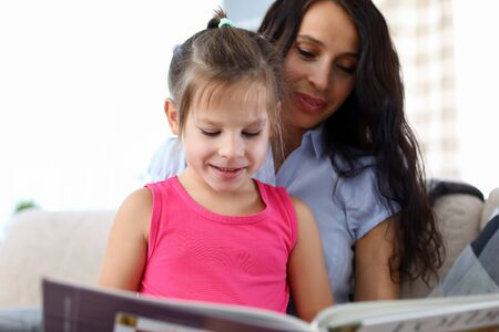 Portrait of smiling child looking at book with interest. Happy woman teaching daughter to read. Little kid sitting on mother knees. Motherhood and friendly family concept