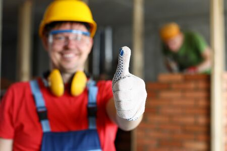 Happy smiling male worker showing thumb up gesture close-up. Fine house renovation or best contractors service concept