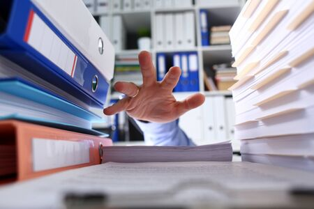 Among folders and documents mans hand seeks help. Multitasking absorbs energy and time. Habit putting off for later leads to disorganization. Failure to meet deadlines. Lot work and outstanding tasks Banque d'images