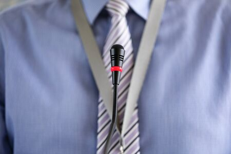 Man wearing necktie standing at conference microphone close-up Archivio Fotografico