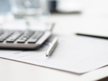 On office document lies silver pen and calculator. Financial calculator help with working with banks. Feature calculating interest on loan or deposit. Settlements on mortgage, deposits, leasing