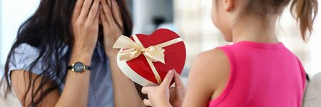 Cute little girl giving her mom birthday present packed in heart shaped red box close-up. Sweet family lifestyle and happiness concept
