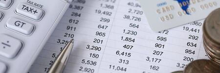 Close-up of plurality of numbers on spreadsheet in columns and rows facing left side. Calculator pen and cash money and credit card on accountant desk. Finance concept