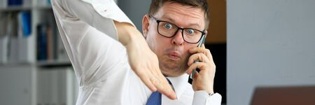 Male executive talking cellphone about bad consequences of world financial crisis for business concept. Businessman demonstrating financial market crash with hands articulation portrait